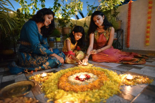 A mother and her two daughters lighting candles for Diwali