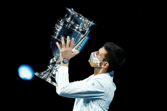 Novak Djokovic of Serbia wears a face mask / covering as he poses with his trophy after being announced as ATP Tour end of year world number one during Day one of the Nitto ATP World Tour Finals at The O2 Arena on November 15, 2020 in London, England.