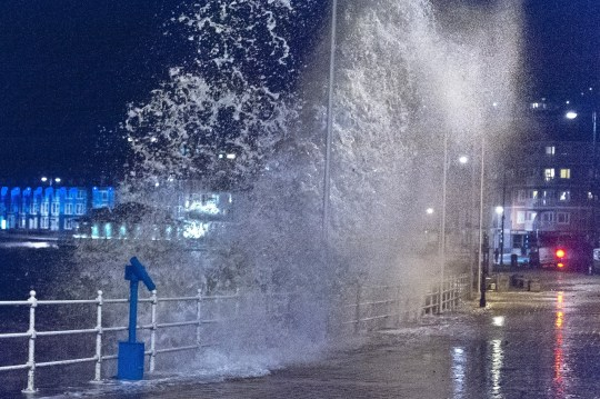 On the evening high tide, gale force winds and massive waves continue to batter the Welsh seaside resort of Aberystwyth in Ceredigion, UK