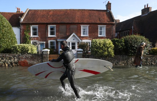 A windsurfer makes carries his board through a flooded street in Bosham, West Sussex