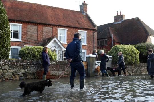 People navigate a flooded street in Bosham, West Sussex