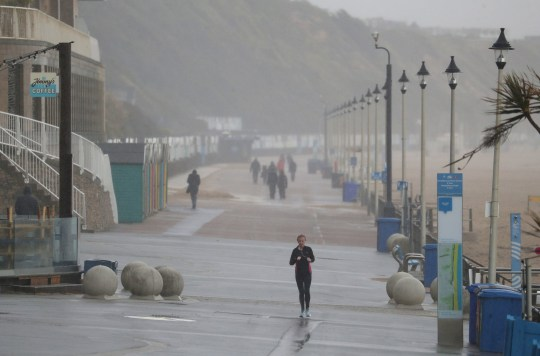 A person jogs along the sea front next to Boscombe beach in Dorset.