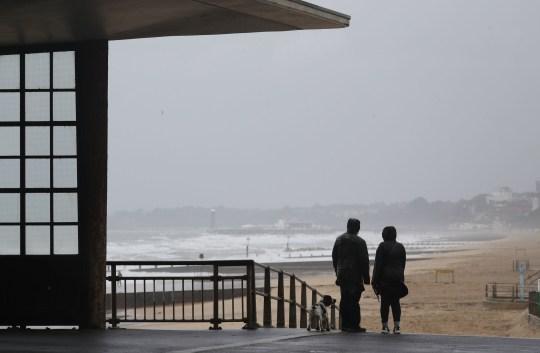 People walk their dog on Boscombe beach in Dorset