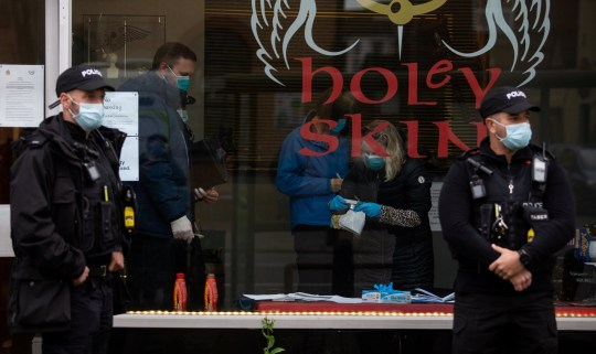 This picture was previously sent with an incomplete caption - many apologies. Police raid the tattoo parlour Holey Skin in Bristol that had refused to shut for lockdown, November 13 2020. Aron Walton has been at the centre of a row in Bristol over his refusal to close the doors of his business - during both lockdowns. See SWNS story SWBRtattoo Walton had previously announced that he would be keeping Gloucester Road???s Holey Skin open, in breach of the second coronavirus lockdown.