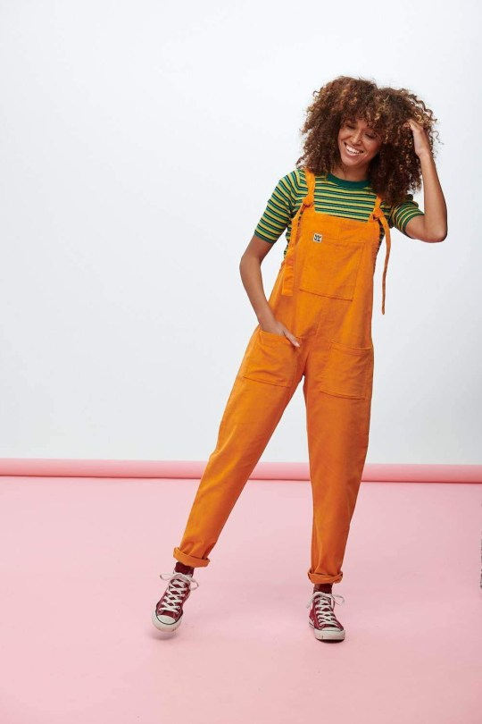 Woman models Lucy & Yak's gender neutral orange dungarees.