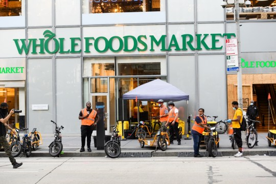 NEW YORK, NEW YORK - JULY 12: Delivery workers stand outside Whole Foods Market in midtown as New York City moves into Phase 3 of re-opening following restrictions imposed to curb the coronavirus pandemic on July 12, 2020. Phase 3 permits the reopening of nail and tanning salons, tattoo parlors, spas and massages, dog runs and numerous other outdoor activities. Phase 3 is the third of four-phased stages designated by the state. (Photo by Noam Galai/Getty Images)