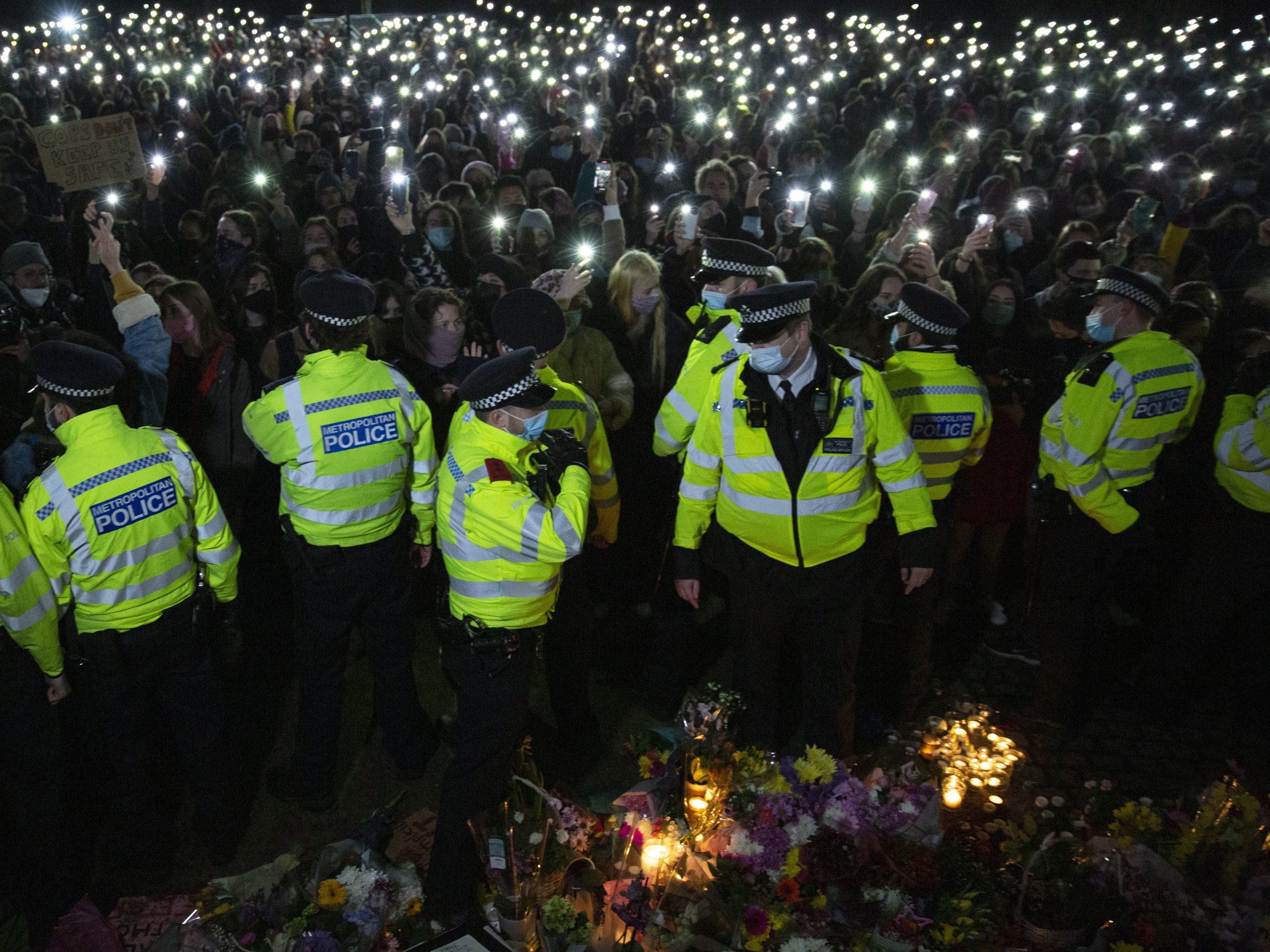 People attend a vigil by a band stand in Clapham Common, London