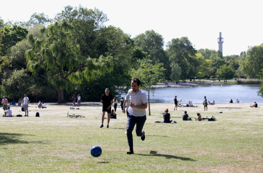 A group of friends play football by the lake in Regent's Park on May 18, 2020 in London, United Kingdom.