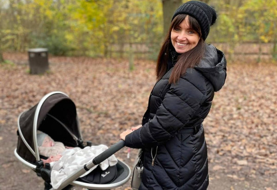 Franchesca Flack walking in the woods with her baby girl in a pram