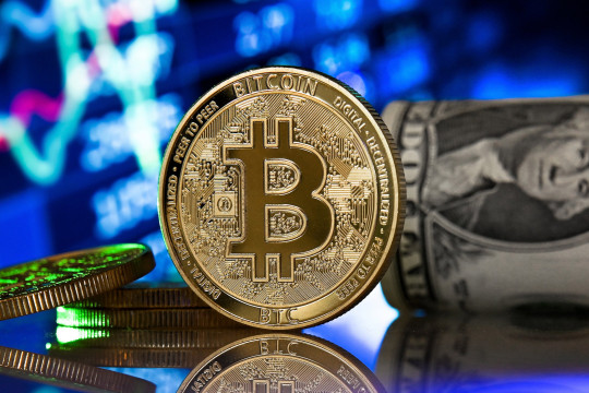 A bitcoin reflects in front of a monitor showing a stock barometer