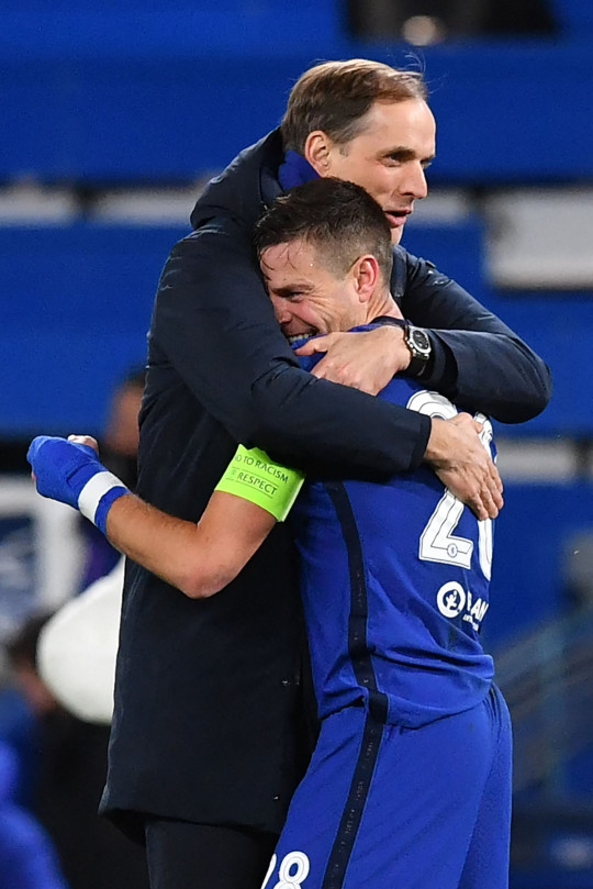Chelsea's German head coach Thomas Tuchel (L) and Chelsea's Spanish defender Cesar Azpilicueta react at the final whistle during the UEFA Champions League round of 16 second leg football match between Chelsea and Atletico Madrid at Stamford Bridge in London on March 17, 2021.