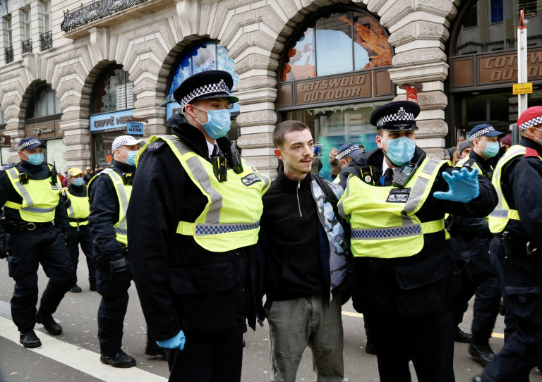 LONDON, UNITED KINGDOM - MARCH 20: People gather to stage a demonstration to protest against the ongoing restrictions against the novel coronavirus (Covid-19), in London, United Kingdom on March 20, 2021. Police officers detained some of anti-lockdown protesters during the protest. (Photo by Hasan Esen/Anadolu Agency via Getty Images)