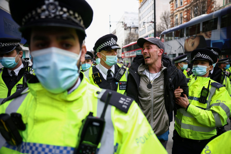 Police officers detain a demonstrator during a protest against the lockdown, amid the spread of the coronavirus disease (COVID-19), in London, Britain March 20, 2021. REUTERS/Henry Nicholls