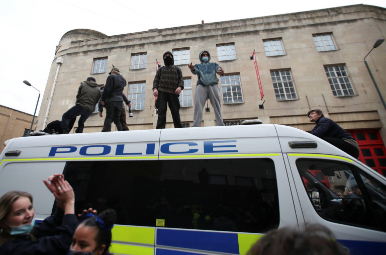 SENSITIVE MATERIAL. THIS IMAGE MAY OFFEND OR DISTURB Demonstrators climb a police van as they take part in a protest against a new proposed policing bill, in Bristol, Britain, March 21, 2021. REUTERS/Peter Cziborra