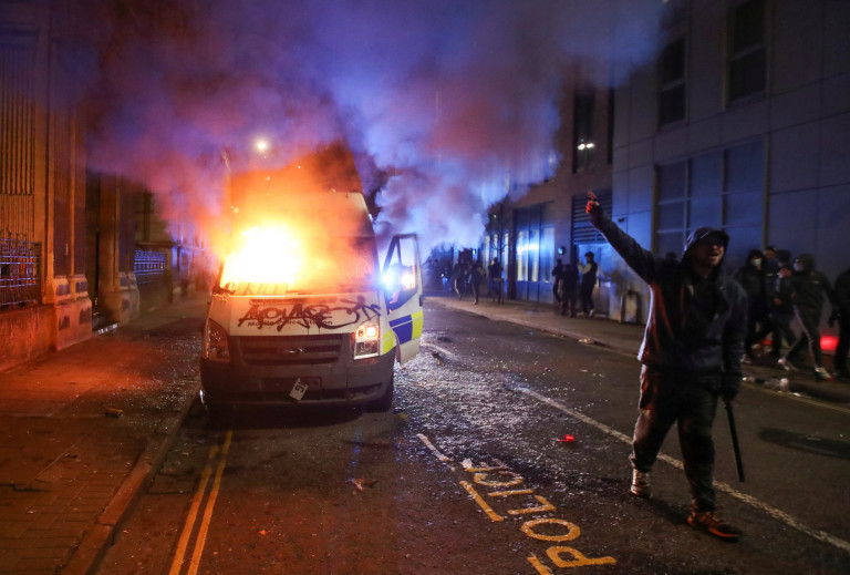 A demonstrator gestures near a burning police vehicle during a protest against a new proposed policing bill, in Bristol, Britain, March 21, 2021. REUTERS/Peter Cziborra