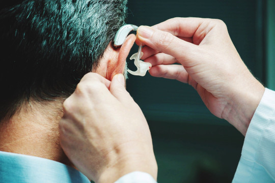 A man is fitted with a hearing aid