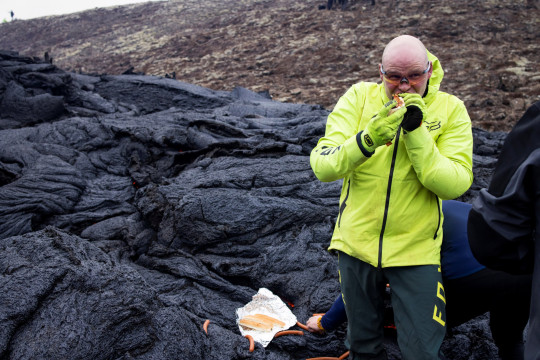 A man eats a hot dog at the volcanic site on the Reykjanes Peninsula following Friday's eruption in Iceland March 21, 2021. Picture taken March 21, 2021. REUTERS/Cat Gundry-Beck NO RESALES. NO ARCHIVES.
