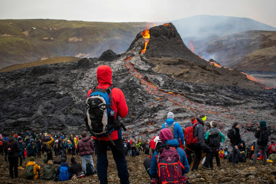 Sunday hikers look at the lava flowing from the erupting Fagradalsfjall volcano some 40 km west of the Icelandic capital Reykjavik, on March 21, 2021. - Weekend hikers took the opportunity Sunday to inspect the area where a volcano erupted in Iceland on March 19, some 40 kilometres (25 miles) from the capital Reykjavik, the Icelandic Meteorological Office said, as a red cloud lit up the night sky and a no-fly zone was established in the area. (Photo by Jeremie RICHARD / AFP) (Photo by JEREMIE RICHARD/AFP via Getty Images)