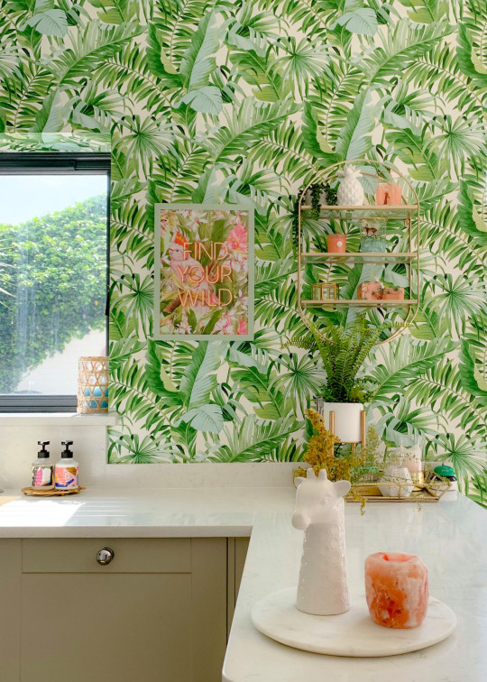 Kitchen with bright green leaf wallpaper white countertops, cermaic giraffe head and pink himalayan salt lamp in foreground