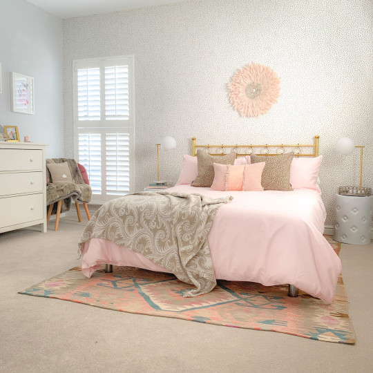 Double bed with pale pink bedding and pink feather wall hanging