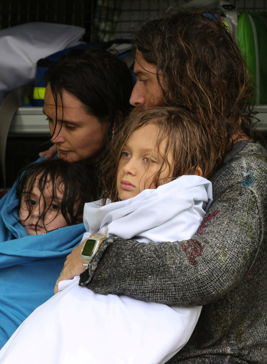 A family receives medical attention after the Marine Rescue boat that rescued them from rising floodwaters capsized in strong currents, as the state of New South Wales experiences widespread flooding and severe weather, in the suburb of Sackville North in Sydney, Australia, March 23, 2021. REUTERS/Loren Elliott