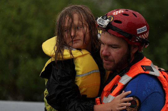 A child is carried to safety by a State Emergency Service member after a Marine Rescue boat rescuing a family from rising floodwaters capsized in strong currents, as the state of New South Wales experiences widespread flooding and severe weather, in the suburb of Sackville North in Sydney, Australia, March 23, 2021. REUTERS/Loren Elliott