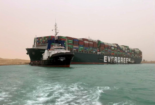(FILES) A handout picture released on March 24, 2021 shows the Taiwan-owned MV Ever Given, a 400-metre- (1,300-foot-)long and 59-metre wide vessel, lodged sideways and impeding all traffic across the waterway of Egypt's Suez Canal. - A giant container ship ran aground in the Suez Canal after a gust of wind blew it off course, the vessel's operator said on March 24, 2021, bringing marine traffic to a halt along one of the world's busiest trade routes. (Photo by - / Suez CANAL / AFP) (Photo by -/Suez CANAL/AFP via Getty Images)