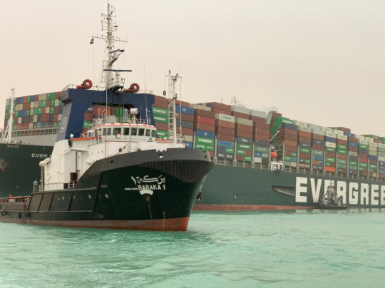 A handout picture released on March 24, 2021 shows the Taiwan-owned MV Ever Given, a 400-metre- (1,300-foot-)long and 59-metre wide vessel, lodged sideways and impeding all traffic across the waterway of Egypt's Suez Canal. - A giant container ship ran aground in the Suez Canal after a gust of wind blew it off course, the vessel's operator said on March 24, 2021, bringing marine traffic to a halt along one of the world's busiest trade routes. (Photo by Marina PASSOS / Suez CANAL / AFP) (Photo by MARINA PASSOS/Suez CANAL/AFP via Getty Images)