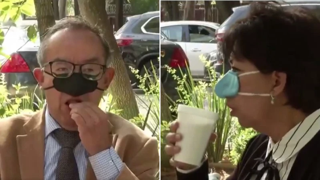 A man and a woman eat and drink wearing the nose-only 'eating mask.'