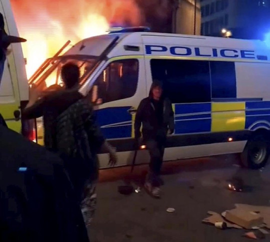 Video grab of a suspect placing a burning card under a police van during the Bristol 'Kill the Bill' disorder in the city on Sunday. See SWNS story SWBRfire. Cops have released this video from the Bristol riots of a suspect placing burning card under a police van - with officers inside. The footage was taken during the violent 'Kill the Bill' disorder in the city on Sunday. It shows the moment a lit item was placed under a police van while a police officer was inside. The officer has described first hearing on the radio how colleagues were being injured outside the Bridewell police station.