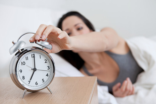 A woman in bed reaches for her alarm clock