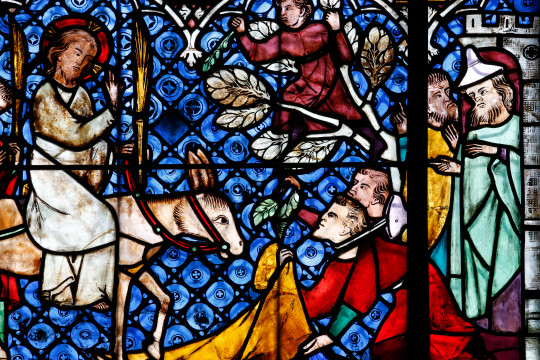 Stained glass window of Jesus arriving at Jerusalem.