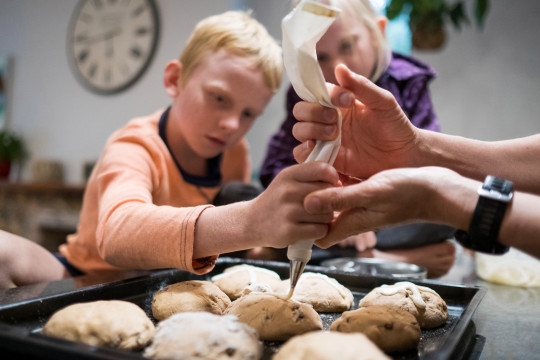 Kids help decorate the hot cross buns