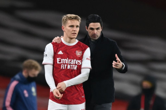 Arsenal's Norwegian midfielder Martin Odegaard (L) gets instructions from Arsenal's Spanish manager Mikel Arteta (R) as he comes on as a substitute during the English Premier League football match between Arsenal and Manchester United at the Emirates Stadium in London on January 30, 2021.
