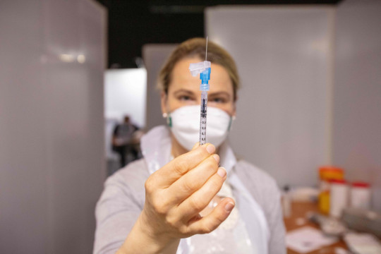 A healthcare professional prepares a dose of the Pfizer/BioNTech Covid-19 vaccine. The UK is looking at donating surplus vaccines to Ireland.
