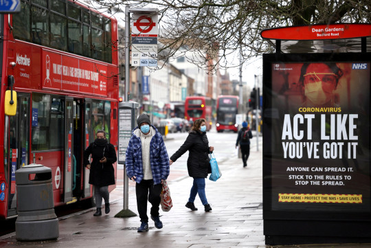 FILE PHOTO: People get off the bus on Ealing's high street where the new SARS-CoV-2 coronavirus variant originating from South Africa has been located, in West London, Britain February 2, 2021. REUTERS/Henry Nicholls/File Photo