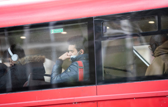 LONDON, ENGLAND - OCTOBER 15: A passenger in a bus wears a face mask on October 15, 2020 in London, England. The city is on course for an imminent tightening of coronavirus restrictions, as cases continue to rise in Britain and its response fragments. (Photo by John Phillips/Getty Images)