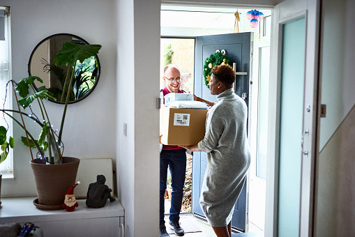 Delivery man handing over cardboard box to female customer