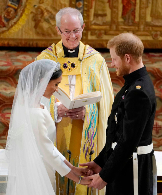 Britain's Prince Harry, Duke of Sussex (R) and US actress Meghan Markle (L) stand facing each other hand-in-hand before Archbishop of Canterbury Justin Welby (C) during their wedding ceremony in St George's Chapel, Windsor Castle, in Windsor, on May 19, 2018.