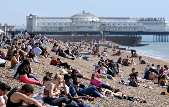 BRIGHTON, ENGLAND - MARCH 30: Sunbathers enjoy the beach as a spell of hot weather coincides with lockdown restrictions being eased on March 30, 2021 in Brighton, England. Forecasters are predicting temperatures of 22C (72F), and with the easing of coronavirus lockdown rules many people will be heading for the outdoors. (Photo by Karwai Tang/Getty Images)