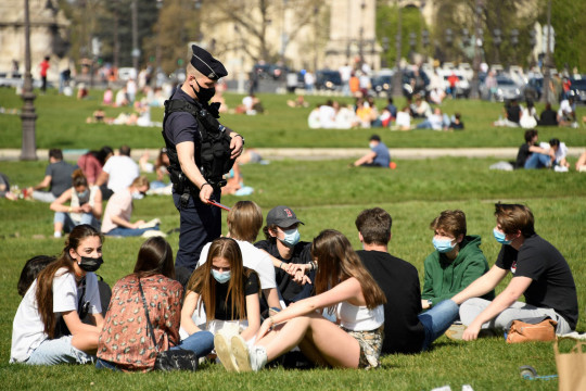 TOPSHOT - Police officers control people enjoying a sunny spring day on the grassin front of the Hotel des Invalides in Paris, amidst the coronavirus pandemic, on March 31, 2021. (Photo by BERTRAND GUAY / AFP) (Photo by BERTRAND GUAY/AFP via Getty Images)