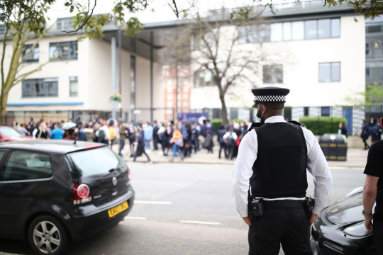 A police officer outside Pimlico Academy School, west London, where students have staged a walkout in protest over a school uniform policy that they claim is discriminatory and racist. Picture date: Wednesday March 31, 2021. PA Photo. Photo credit should read: Aaron Chown/PA Wire