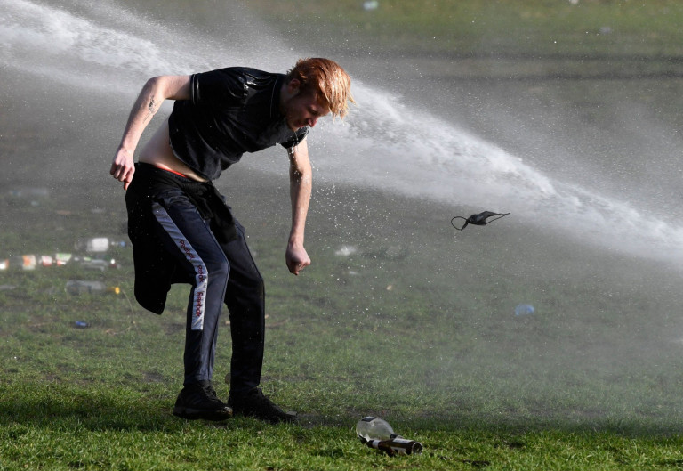 A party goer in Brussels bends down to pick up something from the floor, while a water cannon is blasted behind him.
