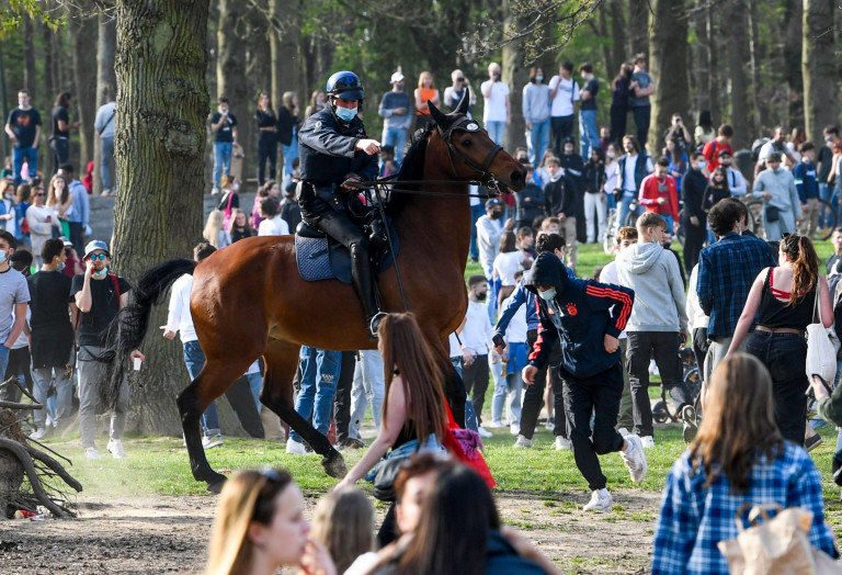 Police on horse back break up a party in a Brussels park.