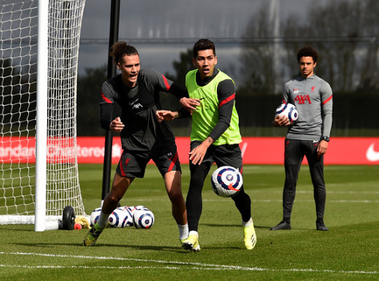 Rhys Williams and Roberto Firmino fight for the ball in Liverpool training