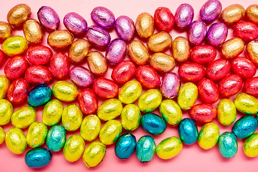 Directly above shot of colourful chocolate easter eggs on pink background