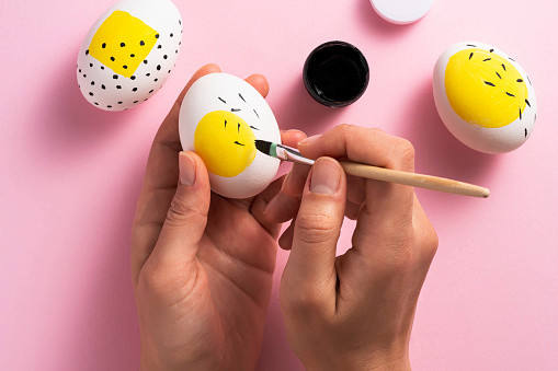 Painting easter eggs on a pink background