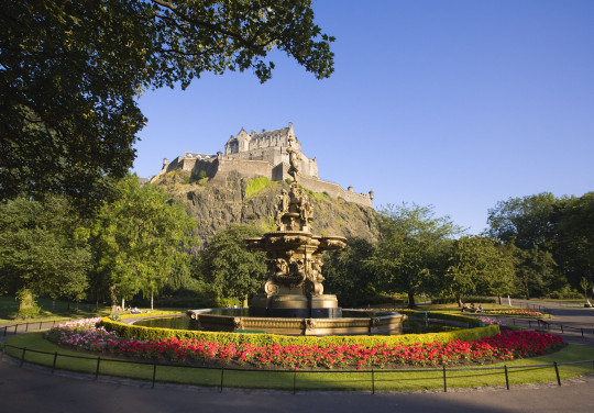 Edinburgh Castle bathed in late afternoon sunshine with the Ross Fountain in Princes Street Gardens