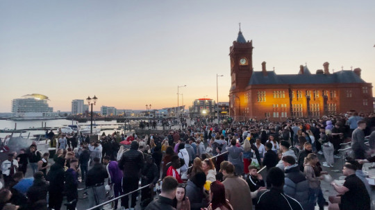Large gathering at Cardiff Bay party amid lockdown easing.