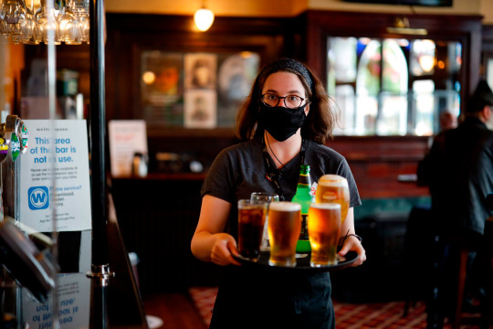 A member of bar staff wearing PPE (personal protective equipment) in the form of a face mask, carries drinks inside the Wetherspoon pub, Goldengrove in Stratford in east London on July 4, 2020, as restrictions are further eased during the novel coronavirus COVID-19 pandemic.